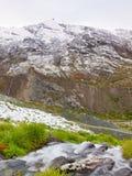 Primera nieve en la región turística de las montañas Prado verde fresco con la corriente de los rápidos Picos de las montañas de  Foto de archivo libre de regalías