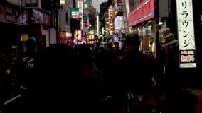 Primera persona POV que camina abajo de una calle secundaria en la noche en Tokio Japón almacen de metraje de vídeo