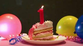 Primera torta de cumpleaños feliz y número rosado una vela con los globos almacen de metraje de vídeo