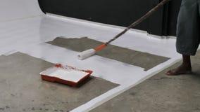 Primera vez de la resina de epoxy de pintura y de capa del trabajador en piso concreto almacen de metraje de vídeo