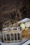 Primeras ramitas de la primavera en botellas en cesta con los huevos de Pascua en fondo Fotografía de archivo libre de regalías