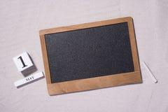 Primero de mayo, el 1 de mayo 1 de mayo bloques de madera blancos con la pizarra negra sobre fondo arenoso Concepto del Día del T Imágenes de archivo libres de regalías