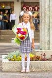 Primero-graduador del bebé del cultivador con el ramo de flores en la escuela Imagen de archivo libre de regalías