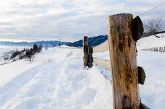 Primero plano de madera de las cercas Mountain View del invierno en el amanecer, el ` del sol Foto de archivo libre de regalías