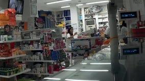 Primero plano real de la farmacia, mujer joven que trabaja en contador de la caja registradora almacen de metraje de vídeo