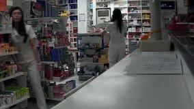 Primero plano real de la farmacia, mujer joven que trabaja tomando la nota de la prescripción almacen de metraje de vídeo