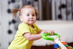 Primeros pasos de la niña en caminante del bebé Imágenes de archivo libres de regalías