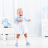 Primeros pasos del bebé que aprenden caminar Imagen de archivo libre de regalías