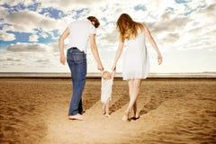 Primeros pasos del niño La familia feliz está ayudando a tomas del bebé primero Foto de archivo libre de regalías