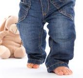 Primeros pasos - pequeños pies del bebé en vaqueros aislados en blanco con Fotos de archivo libres de regalías
