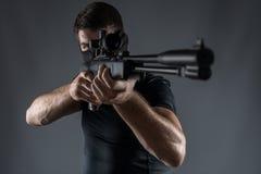 Primi piani dell'uomo alla tendenza del fucile di tiratore franco isolato fotografia stock