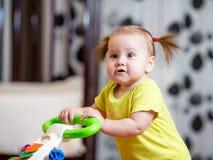 Primi punti della ragazza del piccolo bambino nel camminatore del bambino immagine stock libera da diritti