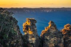 Primi raggi di sole di mattina a tre sorelle in montagna blu fotografia stock libera da diritti