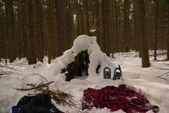 Primitieve die bushcraftschuilplaats met sneeuw wordt behandeld Royalty-vrije Stock Afbeeldingen