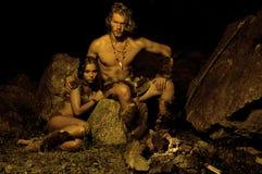 Primitieve man en zijn vrouwenzitting dichtbij de brand in het hol stock fotografie