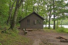 Primitiv kabin på ett Forested Lakeshore Arkivbilder