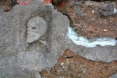 Primitiv skalle- och korslagda benknotorlättnad på gammal kyrkogård fäktar Arkivfoton