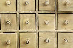 Primitive apothecary drawer cabinet. Drawers of primitive vintage grunge wood apothecary cabinet royalty free stock photo