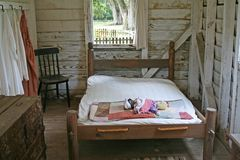 Primitive bedroom. With bed, chest and chair Stock Photography