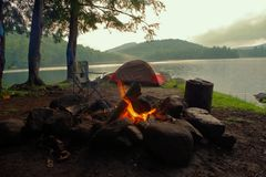 Primitive Bushcraft Campsite with a tent, chair, chair and campfire in the Adirondack Mountain Wilderness. Primitive Bushcraft campsite with a tent, chair royalty free stock image
