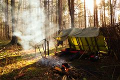 Primitive Bushcraft lean to Shelter with campfire in the Wilderness. Smoke rising up from the fire in the forests of upstate New York royalty free stock photography
