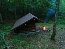 Primitive Bushcraft Adirondack lean to Shelter with campfire in the Wilderness. Primitive Bushcraft Lean To Shelter with campfire in the Wilderness. Smoke royalty free stock photo