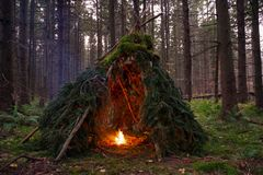 Primitive Bushcraft Shelter with campfire in the Wilderness. Teepee like shelter in the forests of upstate New York Stock Image