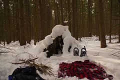 Primitive bushcraft shelter covered with snow. royalty free stock images