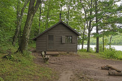 Primitive Cabin on a Forested Lakeshore Stock Images