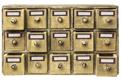 Primitive drawer cabinet. Primitive wooden apothecary or catalog cabinet with partially open drawers and blank labels in bronze holders Royalty Free Stock Photos