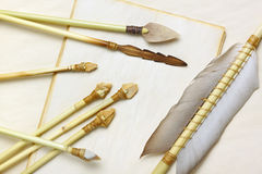 Primitive hunting and fishing arrows. With flint stone, wood and bone arrowheads over aged paper sheets Royalty Free Stock Photography