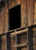 Primitive ladder and door in an old wooden barn. Primitive ladder leading to mysterious dark entry - upper level of an old weathered barn Stock Photo