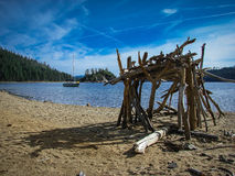 Primitive looking stick hut on beach of Lake Tahoe's Emerald Bay with a sailboat in background on the lake Stock Photo