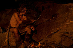 Primitive man draws on a stone. Primitive man painting cave paintings Stock Photography