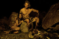 Primitive man and his woman sitting near the fire in the cave. Primeval couple sitting near the fire Stock Photography