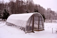Primitive plastic  greenhouse in winter farm garden Royalty Free Stock Images