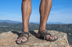 Primitive sandals. Closeup of man's weathered feet in primitive leather sandals stepping on rock high up on mountain with blue sky in background Royalty Free Stock Images