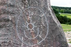 Primitive stone inscription of Sun, Moon and Venus. With summer landscape in the background Royalty Free Stock Images