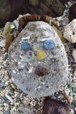 Primitive stone sculpture of a face Stock Images
