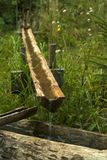 Primitive water pipe from wooden gutters. Primitive water supply system from wooden gutters leading from the spring stock photos