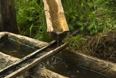 Primitive water pipe from wooden gutters. Primitive water supply system from wooden gutters leading from the spring stock images