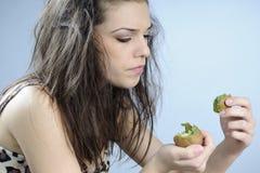 Primitive woman analyzing kiwi Stock Images