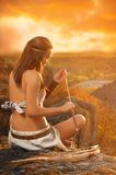 Primitive woman  holding a bow and arrow. Amazon woman Stock Photography