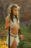 Primitive woman  holding a spear. Amazon woman Royalty Free Stock Image