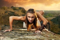 Primitive woman on a rock at the sunset. Amazon woman Royalty Free Stock Images