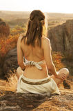 Primitive woman sitting on a rock at the sunset. Amazon woman Stock Image