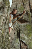 Primitive woman standing on a rock and holding a bow. Amazon woman. Woman warrior. Amazon woman. Warrioress Stock Photos