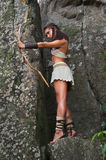 Primitive woman standing on a rock and holding a bow. Amazon woman Stock Photography
