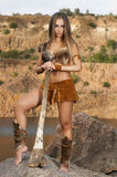 Primitive woman standing on a rock. Primitive woman holding a club and looks into the distance Stock Image
