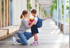 Primo giorno al banco la madre conduce la ragazza della scuola del piccolo bambino nella f fotografie stock libere da diritti